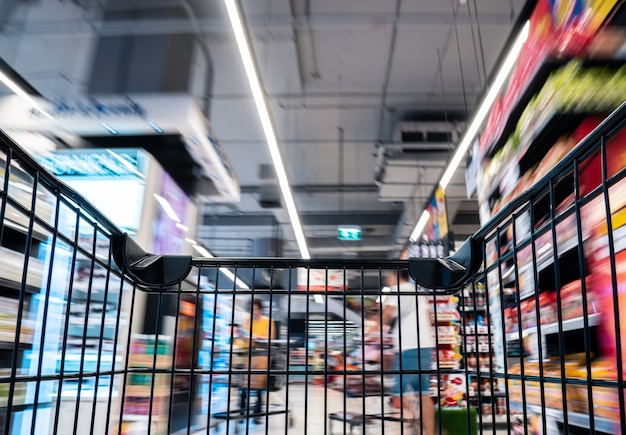 Moviendo el carrito de compras negro vacío con movimiento en el pasillo del supermercado