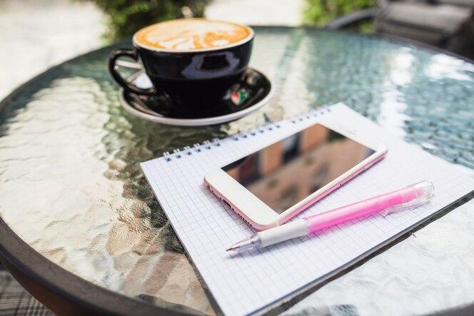 Móvil en el cuaderno y bolígrafo con café en una mesa al aire libre
