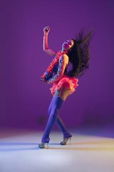 Movimiento de baile. modelo morena hawaiana sobre fondo de estudio púrpura en luz de neón.