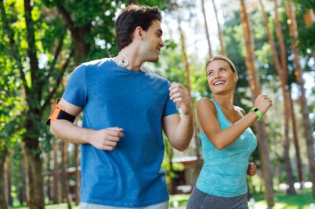 El movimiento es vida. gente deportiva alegre sonriendo el uno al otro mientras corren juntos en el parque Foto Premium