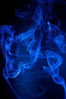 Movimiento de humo azul sobre fondo negro.
