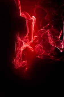 Movimiento de humo rojo sobre fondo negro.