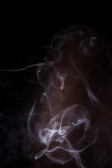 Movimiento de humo sobre fondo negro.