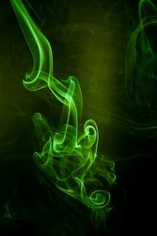 Movimiento de humo verde sobre fondo negro.