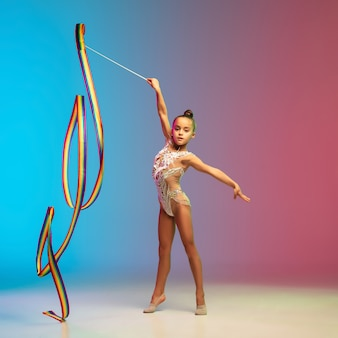 Movimiento. niña caucásica, entrenamiento de gimnasta rítmica, realizar aislado