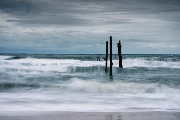 Movimiento de onda golpeando el puente de madera decadencia en la playa en tiempo tormentoso