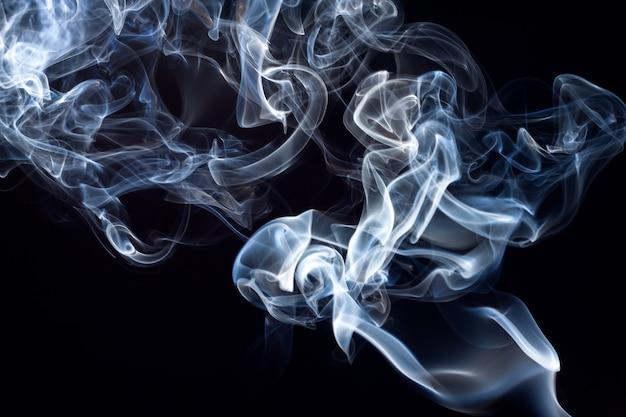 Movimiento del resumen de humo azul y blanco sobre fondo negro