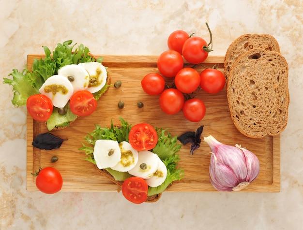 Mozarella con tomates en una tabla de madera