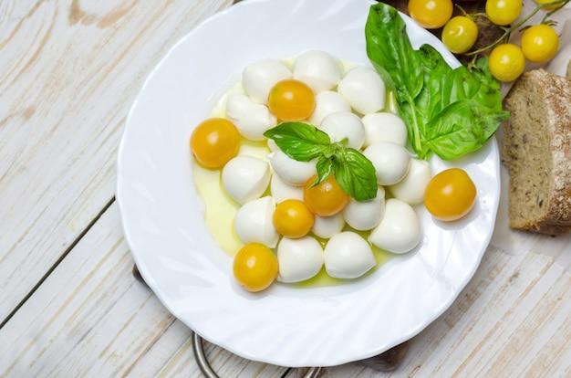Mozzarella fresca con tomate amarillo y albahaca.