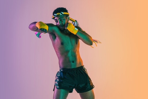 Muay thai joven ejercicio de boxeo tailandés en pared degradada