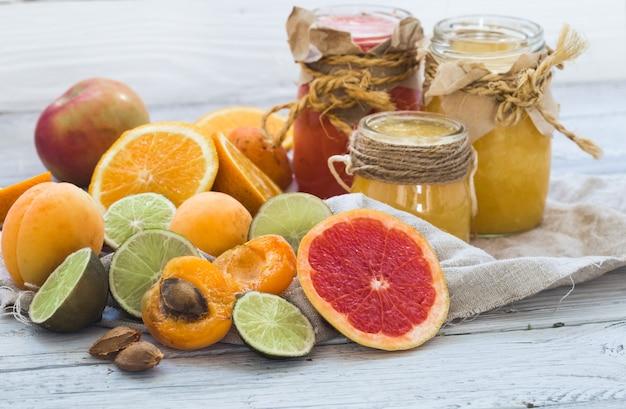 Mucha fruta fresca, cortada en un hermoso fondo de madera, bebida de fruta fresca, mermelada, comida sabrosa y saludable