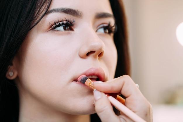 Muchacha abre sus ojos con pestañas largas mientras que la mujer pinta sus labios