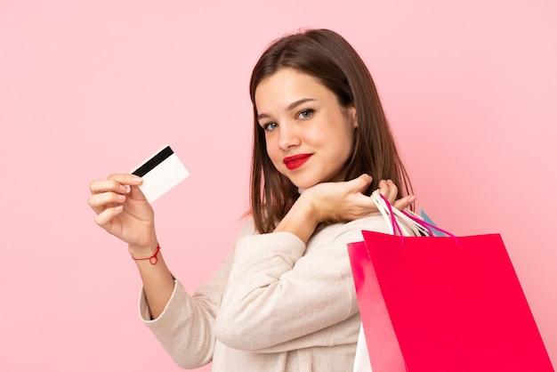 Muchacha adolescente aislada en la pared rosada que sostiene bolsos de compras y una tarjeta de crédito