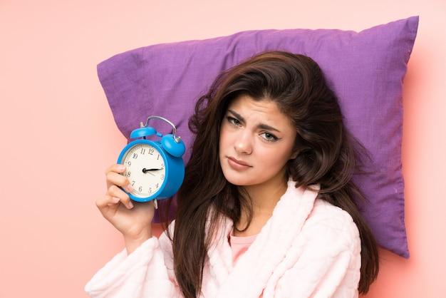 Muchacha del adolescente en la bata sobre el backgrounnd rosado y subrayó sostener el reloj del vintage