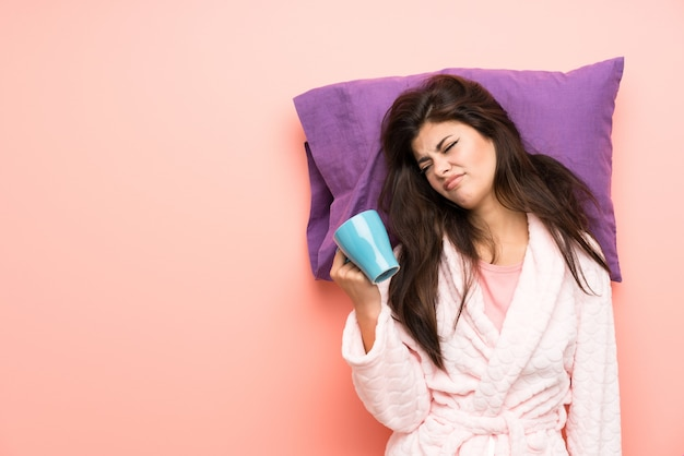 Muchacha del adolescente en la bata sobre backgrounnd rosado y subrayó y sosteniendo una taza de café
