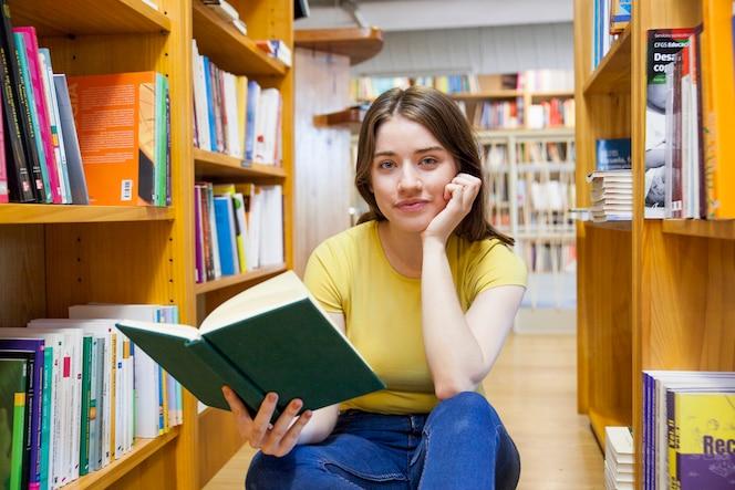 Muchacha adolescente con el libro que mira la cámara entre los estantes
