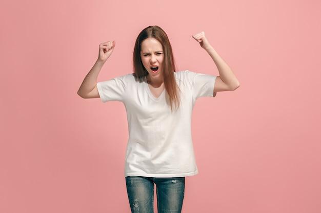 Muchacha adolescente enojada que se coloca en la pared azul de moda. retrato femenino de medio cuerpo. las emociones humanas, el concepto de expresión facial. vista frontal.