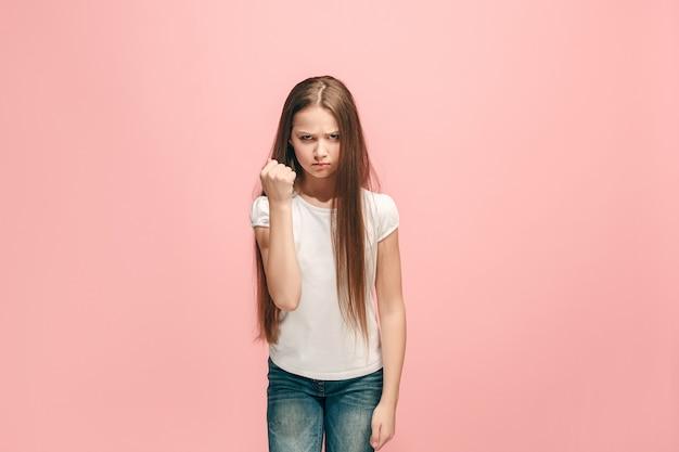 Muchacha adolescente enojada que se coloca en la pared rosada de moda. retrato femenino de medio cuerpo. las emociones humanas, el concepto de expresión facial. vista frontal.