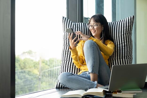 La muchacha adolescente escucha música en la lista de reproducción con auriculares.