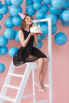 Muchacha adolescente feliz que sostiene la torta acodada del unicornio adornada con el primer de los merengues.