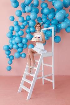 Muchacha adolescente feliz que sostiene la torta de cumpleaños, sentándose en la escalera blanca en fondo rosado