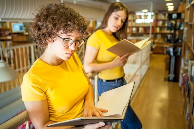 Muchacha adolescente inteligente leyendo cerca de amigo