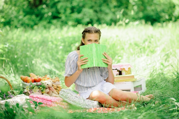 La muchacha adolescente lee un libro en el parque en la naturaleza. la niña hizo un picnic en la naturaleza y se está preparando para la escuela. la niña se cubrió la cara con un libro.