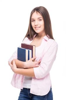 Muchacha del adolescente con los libros aislados en blanco