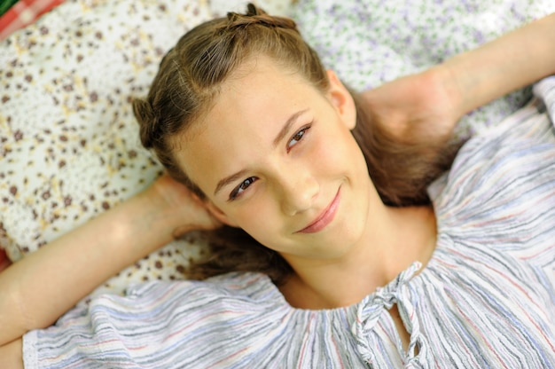 La muchacha adolescente miente en una almohada y mira el cielo. la niña está soñando con algo.