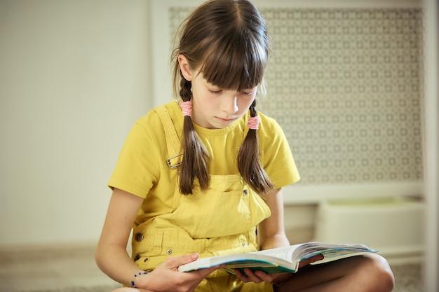 Muchacha adolescente que hace la tarea que se sienta en la alfombra en su sitio