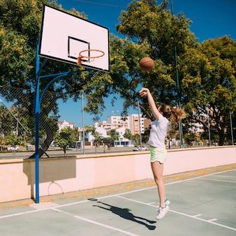 Muchacha adolescente que juega a baloncesto en la echada