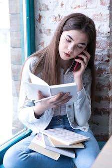 Muchacha del adolescente que se sienta con el libro abierto y que habla en el teléfono móvil