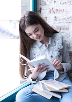 Muchacha del adolescente que se sienta con el libro abierto y que sonríe mientras que lo lee