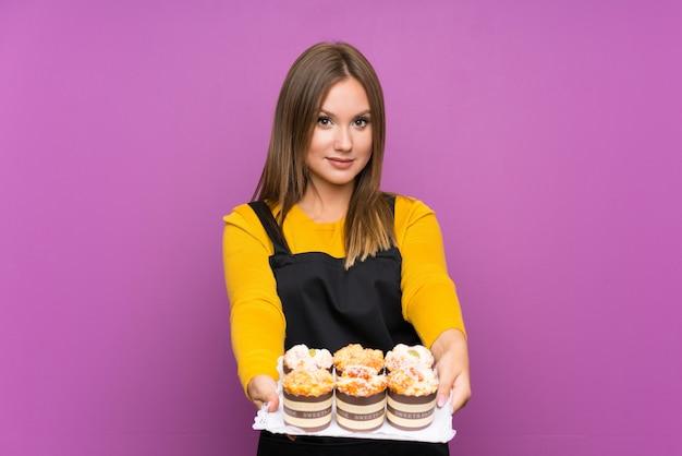 Muchacha adolescente que sostiene muchas mini tortas diferentes sobre aislado