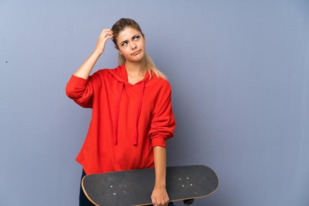 Muchacha adolescente rubia del patinador sobre la pared gris que tiene dudas y con confunde la expresión de la cara