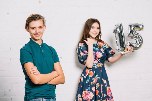 Muchacha adolescente sonriente que sostiene el dedo señalador del globo de la hoja del número 15 hacia el muchacho del cumpleaños