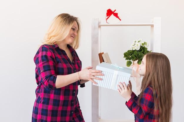 Muchacha adorable del niño con la caja de regalo grande que se lo da a su madre. fiestas, cumpleaños y regalos