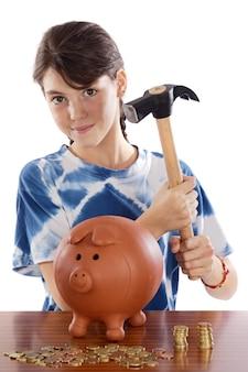 Muchacha adorable que pone sus ahorros en su caja de dinero