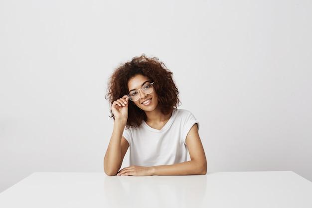 Muchacha africana atractiva joven en vidrios que sonríe sentarse en la tabla sobre la pared blanca. icono de moda futura o diseñador gráfico.