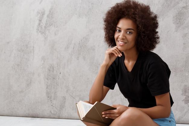 Muchacha africana que se sienta y que sonríe con el libro sobre la pared ligera.