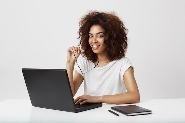 Muchacha africana que sonríe sentado en el wokplace con la computadora portátil.