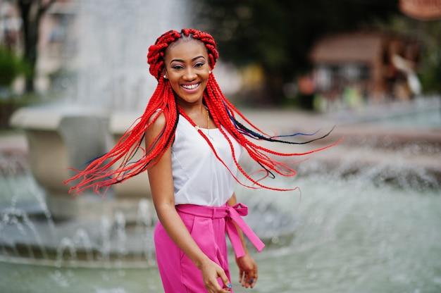 La muchacha afroamericana de moda en pantalones rosados y temores rojos plantea al aire libre contra las fuentes.