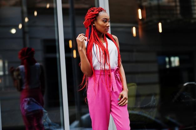 La muchacha afroamericana de moda en pantalones rosados y temores rojos plantea al aire libre.