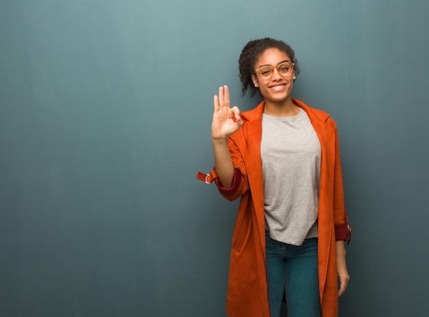 Muchacha afroamericana negra joven con los ojos azules alegres y confiados que hacen gesto aceptable