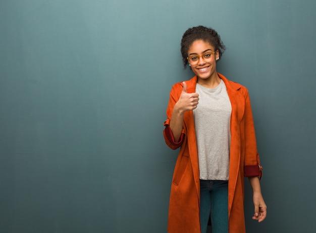 Muchacha afroamericana negra joven con los ojos azules que sonríe y que levanta el pulgar para arriba