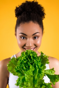 Muchacha afroamericana que sostiene la ensalada aislada.