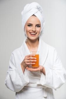 Muchacha en albornoz que bebe el zumo de naranja.
