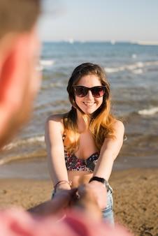 Muchacha alegre atractiva preciosa que lleva a cabo las manos en su novio en la playa
