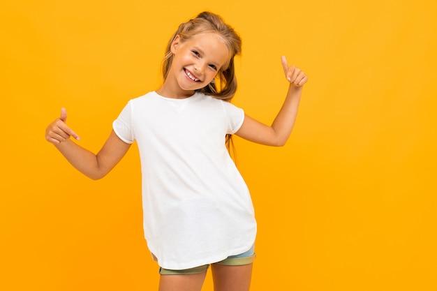 La muchacha alegre en una camiseta blanca sonríe contra un amarillo