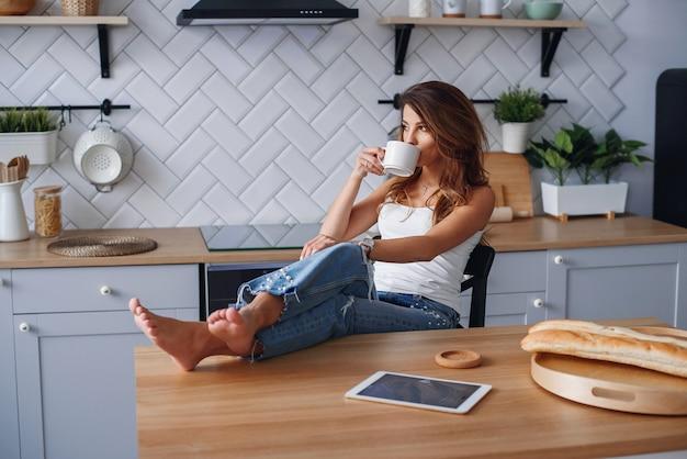 Muchacha alegre en la camiseta blanca usando la tableta mientras que se relaja en una silla en casa en cocina acogedora.